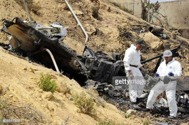 Algerian rescue workers inspect the site of a helicopter crash which killed four people on August 10 in Douera 20 km southwest of Algiers / AFP PHOTO...