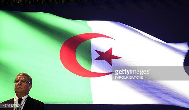 Algerian Secretary General of the National Liberation Front Amar Saadani looks on in front of a national flag displayed on a screen during the 10th...