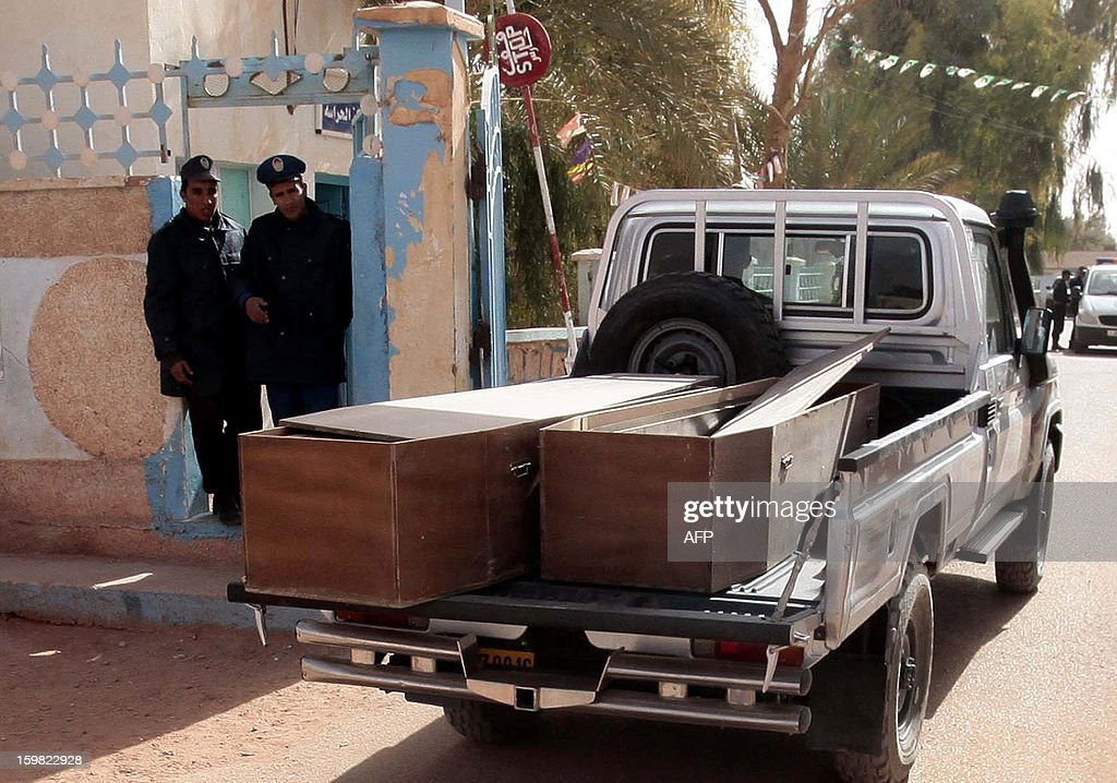 Algerian security personnel monitor as empty coffins are transported to collect victims that were killed during the hostage crisis at a desert gas plant in Algeria's deep south on January 21, 2012 in In Amenas. Two days after Algerian forces ended a hostage crisis at a desert gas plant, the exact toll of those killed in the bloodbath remained unknown, amid fears the total number of hostages who died could reach 50. AFP PHOTO / FAROUK BATICHE