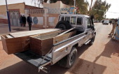 Algerian security personnel monitor as empty coffins are transported to collect victims that were killed during the hostage crisis at a desert gas...