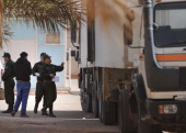 Algerian security personnel monitor as they remove body bags of victims that were killed during the hostage crisis at a desert gas plant in Algeria's...
