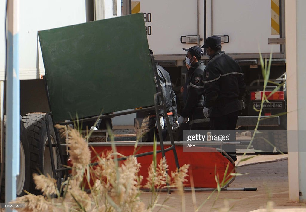 Algerian security personnel use a board and stretcher to conceal from the media as they remove body bags of victims, that were killed during the hostage crisis at a desert gas plant in Algeria's deep south, from a refrigerated truck that is transporting the bodies to hospital for identification in In Amenas on January 21, 2012. Two days after Algerian forces ended a hostage crisis at a desert gas plant, the exact toll of those killed in the bloodbath remained unknown, amid fears the total number of hostages who died could reach 50.