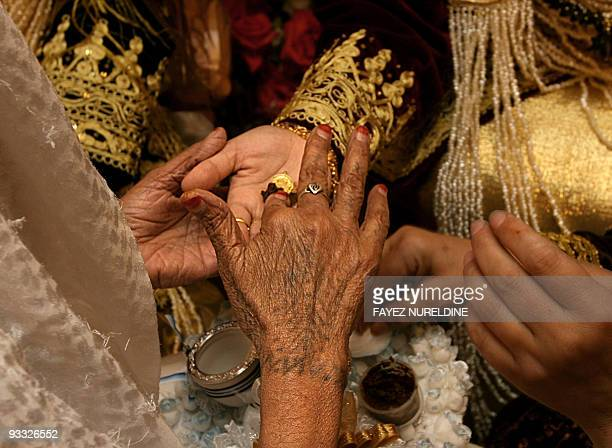 Algerian women decorate the hands of a bride with henna a reddishorange dyestuff during her wedding party in Algiers 08 May 2006 Weddings in Algeria...
