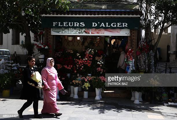 Algerian women walk past a flower shop in the center of Algiers on April 18 2014 AFP PHOTO / PATRICK BAZ