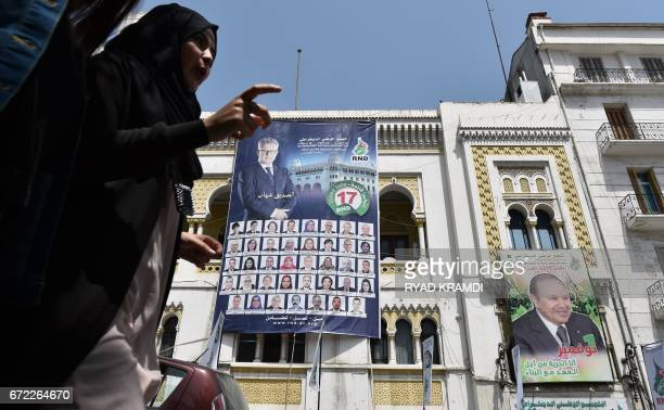 Algerian women walk past election campaign posters of the Rassemblement National Democratique party outside its bureau in the capital Algiers on...
