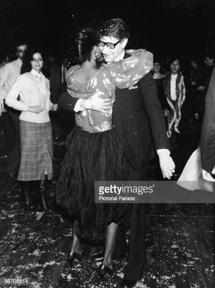 Algerianborn French fashion designer Yves St Laurent dances with American soul singer Diana Ross as other partygoers look on at a fundraiser for...