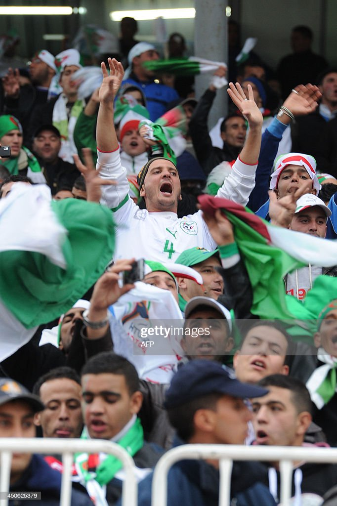 Algerians celebrate victory over Burkina Faso in their World Cup qualifying match on November 19, 2013 in Blida, Algeria. Algeria sealed the fifth and final African zone World Cup qualifying berth, edging their play-off with Burkina Faso on away goals. Algeria got the goal they needed in the 49th minute through skipper Madjid Bougherra off a goal mouth scramble caused by a free-kick. AFP PHOTO/ Farouk BATICHE