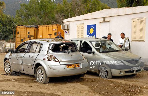 Algerians look at the site of damaged vehicles where a French engineer was killed in a blast near Beni Amrane some 80 kms east of Algiers on June 09...