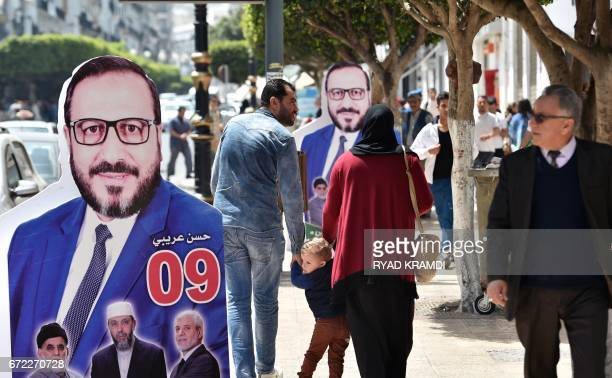 Algerians walk past a an election board of Hassan Aribi who heads the list of candidates in Algiers for 'L'union EnNahdaAdalaBina' Islamist party...