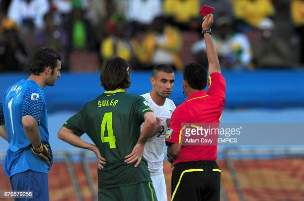 Algeria's Abdelkader Ghezzal is shown a red card by referee Carlos Batres after hand ball