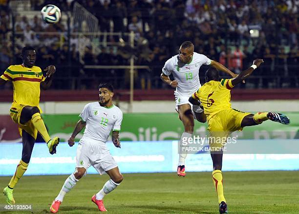 Algeria's defender Carl Medjani and forward Islam slimani vie for the ball during the 2015 African Cup of Nations qualifying football match between...