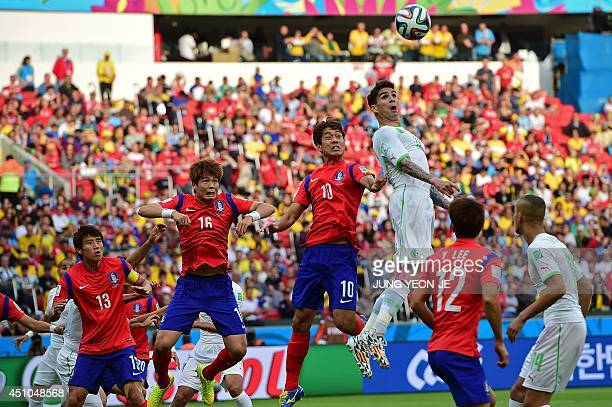 Algeria's defender Carl Medjani jumps to head the ball with South Korea's forward Park ChuYoung and midfielder Ki SungYueng during the Group H...