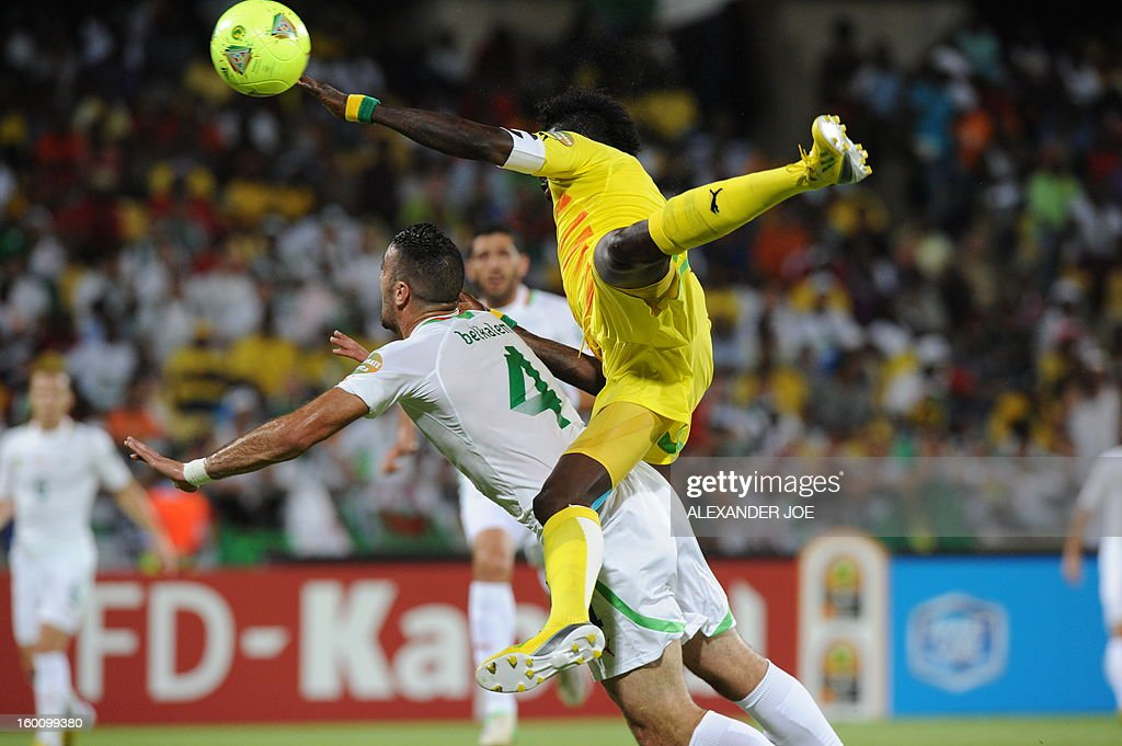 Algeria's defender Essaid Belkalem (L) vies with Togo's forward Emmanuel Adebayor during the 2013 African Cup of Nations football match Algeria vs Togo at Royal Bafokeng stadium in Rustenburg on January 26, 2013.