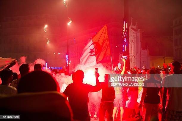 Algeria's football fans celebrate on the Vieux Port on June 22 2014 in Marseille southern France after Algeria defeated South Korea 42 in a FIFA 2014...