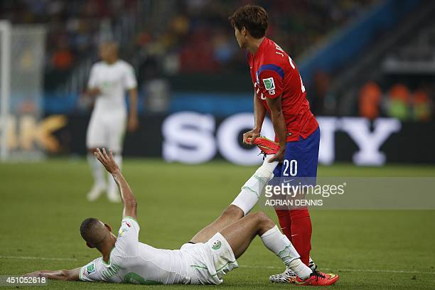 Algeria's forward Islam Slimani is helped by South Korea's defender Hong JeongHo during a Group H football match between South Korea and Algeria at...