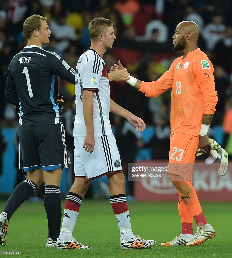 Algeria's goalkeeper Rais Mbohli and Germany's goalkeeper Manuel Neuer shake hands at the end of extratime in the Round of 16 football match between...