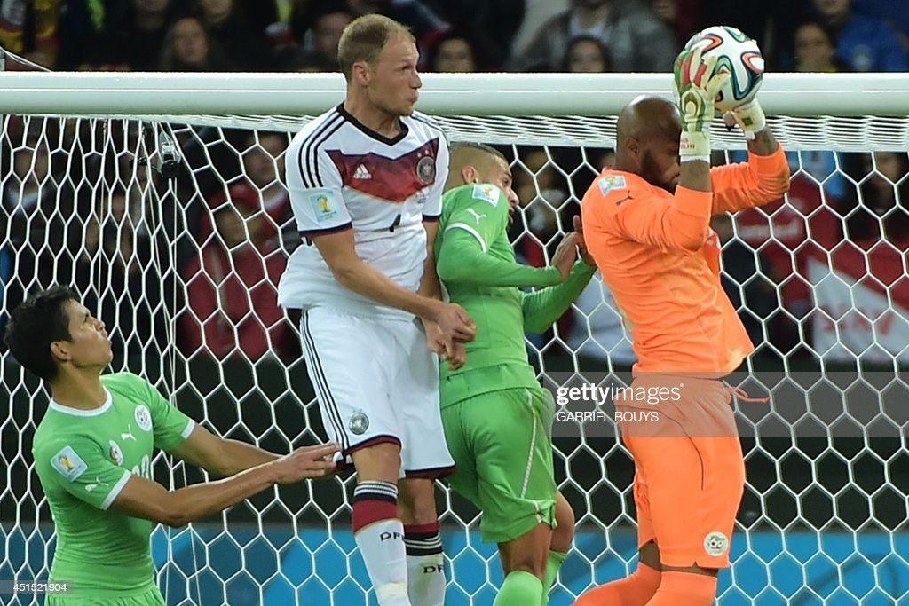 Algeria's goalkeeper Rais Mbohli (R) saves the ball during the Round of 16 football match between Germany and Algeria at Beira-Rio Stadium in Porto Alegre during the 2014 FIFA World Cup on June 30, 2014.