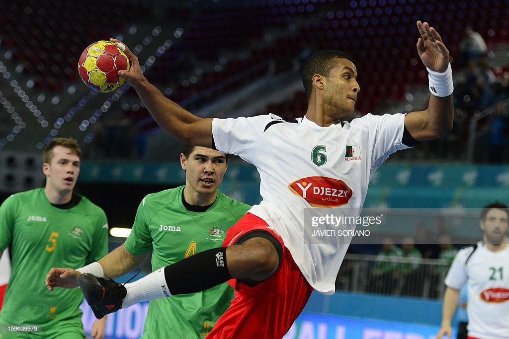 Algeria's left back Messaoud Berkous (R) shoots past Australia's right back Bevan Calvert (L) during the 23rd Men's Handball World Championships preliminary round Group D match Australia vs Algeria at the Caja Magica in Madrid on January 17, 2013. AFP PHOTO/ JAVIER SORIANO