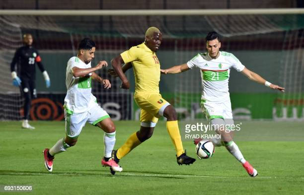Algeria's Saphir Taïder and Ramy Bensebaïni vie with Guinée's Pogba Mathias during their friendly international football match between Algeria and...