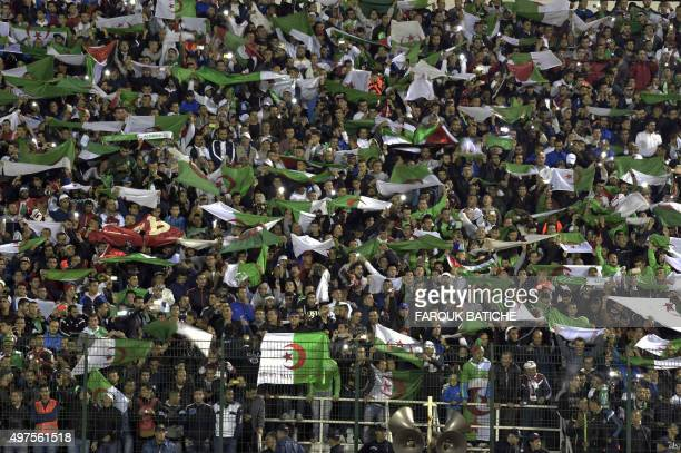 Algeria's supporters wave the country's flag during the FIFA World Cup 2018 qualifying football match between Algeria and Tanzania on November 17...