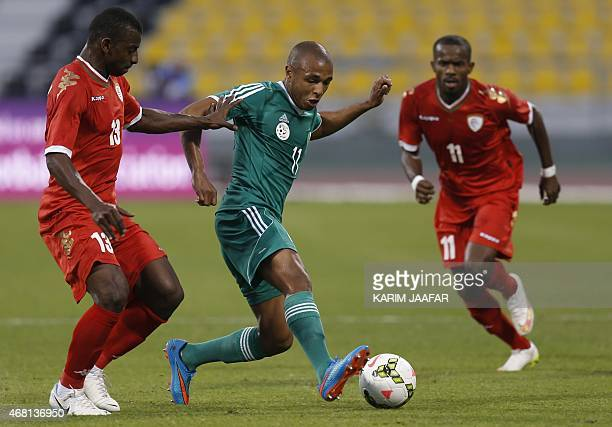 Algeria's Yacine Brahimi dribbles the ball as Oman's Abdul Sallam AlMukhaini tries to tackle during their friendly football match on March 30 2015 at...