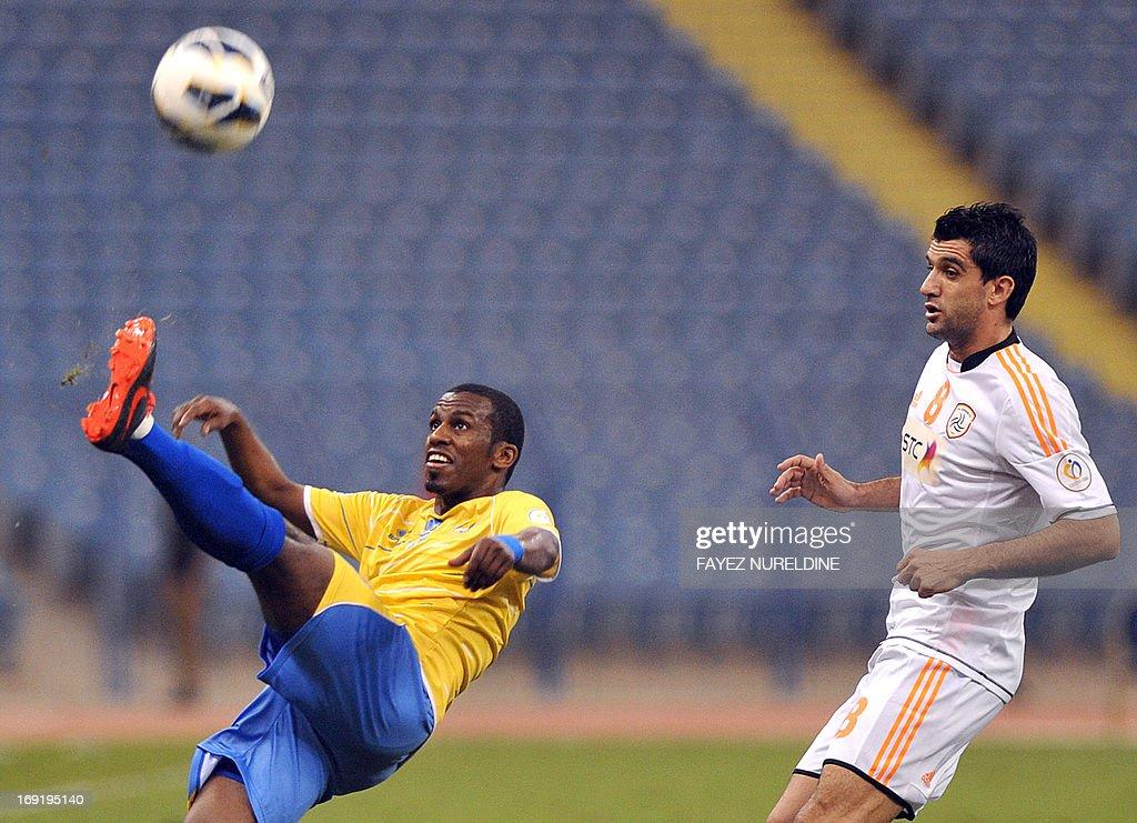 Al-Gharafa Meshal Mubarak (L) hits the ball past Al-Shabab player Fernando Menegazzo (R) during their AFC Champions League football match at King Fahad International stadium in Riyadh, on May 21, 2013.