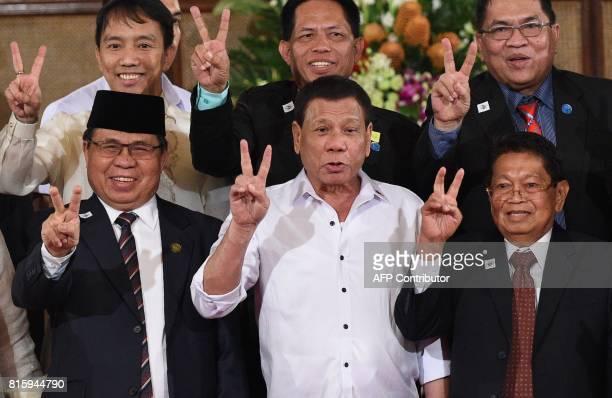 AlHajj Murad chairman of the Moro Islamic Liberation Front Philippine President Rodrigo Duterte and Ghazali Jaafar vice chairman of MILF gesture with...