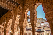 Granada, Spain - March 7, 2014: The Alhambra columns around the Court of the Lions in sunny morning.