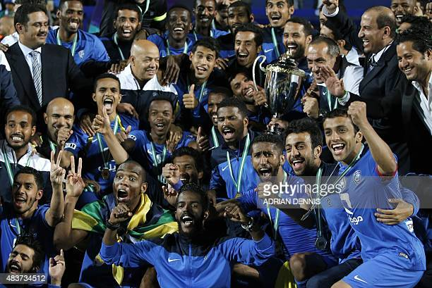 AlHilal players and coaching staff celebrate with the cup after winning the Saudi Super Cup between AlNassr and AlHilal at Loftus road stadium in...