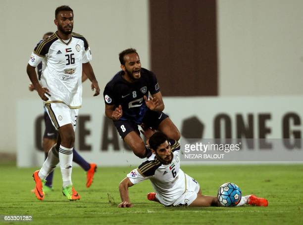 AlHilal's Abdullah Otayf falls after a tackle by AlWahda's Sultan Ali alGhafri during the AFC Champions League group D football match between UAE's...