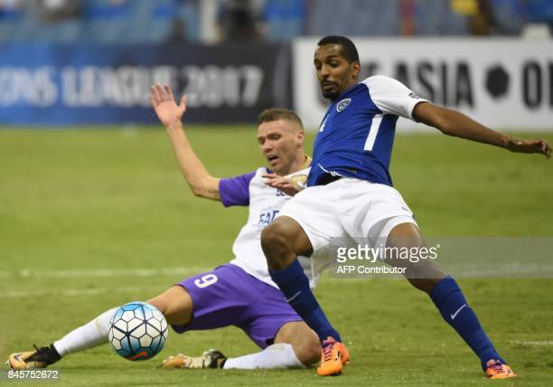 AlHilal's defender Abdullah Zori vies for the ball with AlAin's player Marcus Berg during their AFC Asian Champions League quarter final second leg...