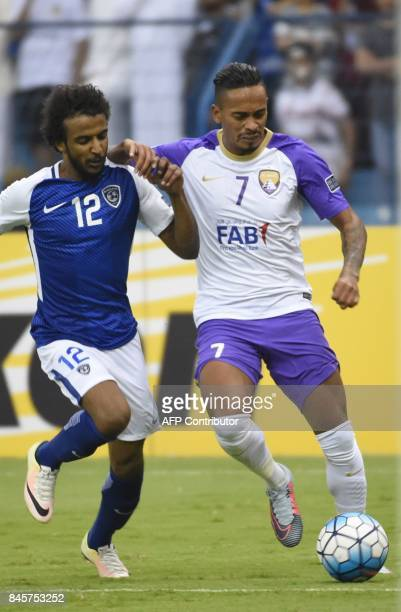 AlHilal's defender Yasir Al Sahrani vies for the ball with AlAin's Caio during their AFC Asian Champions League Group C football match at the King...