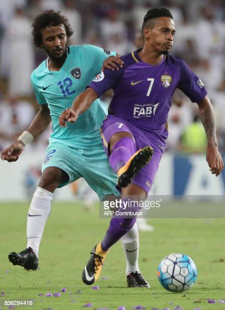 AlHilal's defender Yasser AlShahrani vies for the ball with AlAin's midfielder Caio during their AFC Asian Champions League Group C football match at...