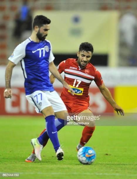 AlHilal's forward Omar Khirbin is marked by Persepolis' defender Sadegh Moharrami during the Asian Champions League semifinal football match between...