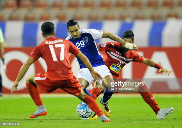 AlHilal's midfielder Salem AlDawsari is marked by Persepolis' defender Sadegh Moharrami during the Asian Champions League semifinal football match...