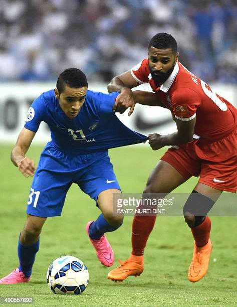 AlHilal's player Ibrahim alBurayk fights for the ball against UAE's AlAhli player Abdelaziz Sangour during their AFC Champions League semifinal...