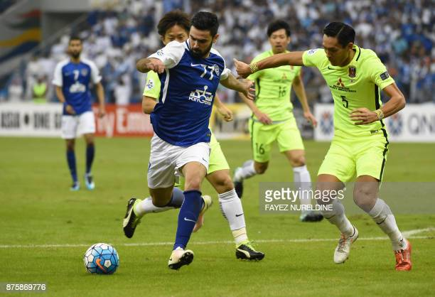 AlHilal's Syrian forward Omar Khribin attempts to shoot as he is marked by Urawa Red's Japanese defender Tomoaki Makino during the Asian Champions...
