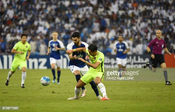 AlHilal's Syrian forward Omar Khribin is marked by Urawa Red's Japanese defender Tomoaki Makino during the Asian Champions League final football...