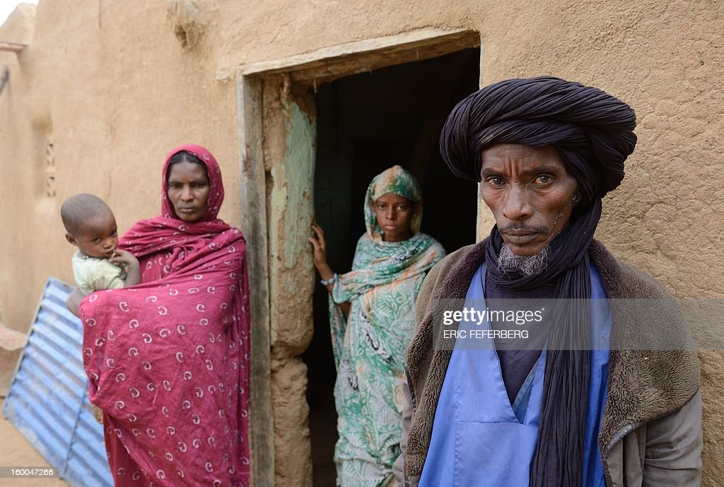 Ali Ag Noh (R) poses on January 25, 2013 with his wife Zahra (2nd L), his daughter (2nd R) and his son Aboubacrim in front of his house in the village of Seribala, 20 kms from Niono, about 350 kms (220 miles) northeast of the capital Bamako after his cousin, who is his wife's brother, Aboubakrim Ag Mohamed, and a cattle rancher, Samba Dicko, were both shot dead on January 24 allegedly by the Malian Army. According to Noh, Mohamed, a Tuareg, and Dicko were shot in the head in Seribala after being accused by two Malian soldiers of being Islamists or aiding Islamists.