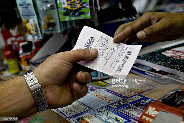 Ali Ahmed right hands a customer a Mega Millions ticket in a deli in New York US on Wednesday Aug 26 2009 The jackpot in the Mega Millions multistate...