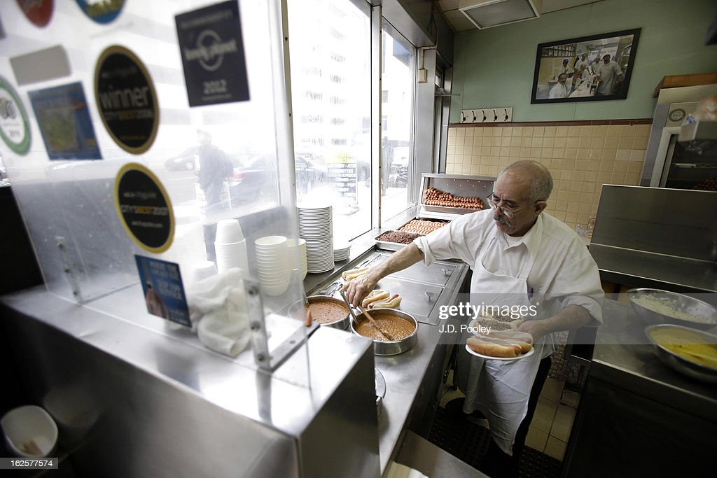 Ali Alhalmi prepares hotdogs at Lafayette Coney Island restaurant February 24, 2013 in Detroit, Michigan. The city of Detroit has faced serious economic challenges in the past decade, with a shrinking population and tax base while trying to maintain essential services. A financial review team issued a finding on February 19 identifying the city as being under a 'financial emergency.' Michigan Gov. Rick Snyder has 30 days from the report's issuance to officially declare a financial emergency, which could result in the governor appointing an emergency financial manager to oversee Detroit's municipal government.