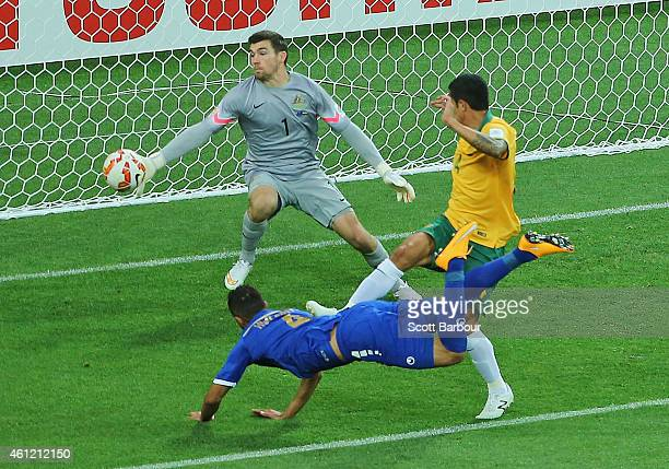 Ali Hussain Fadhel of Kuwait beats Tim Cahill and goalkeeper Mathew Ryan of the Socceroos to score the first goal during the 2015 Asian Cup match...