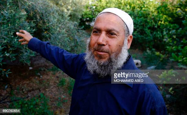 Ali Ishtiwi a 55yearold Palestinian gives an interview with AFP talking about his father Salah Ishtiwi as he walks in his garden in Gaza City on May...