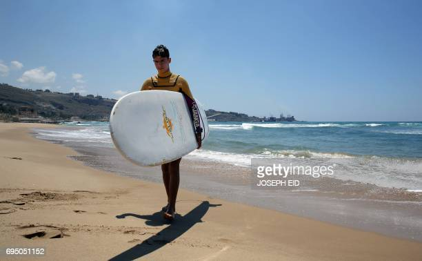 Ali Kassem a 17yearold Syrian refugee carries his surfboard on a beach in the town of Jiyeh south of the Lebanese capital Beirut on May 24 2017 Ali...