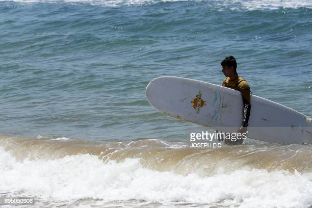 Ali Kassem a 17yearold Syrian refugee carries his surfboard out of the water on a beach in the town of Jiyeh south of the Lebanese capital Beirut on...