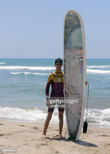 Ali Kassem a 17yearold Syrian refugee poses for a picture holding his surfboard on a beach in the town of Jiyeh south of the Lebanese capital Beirut...