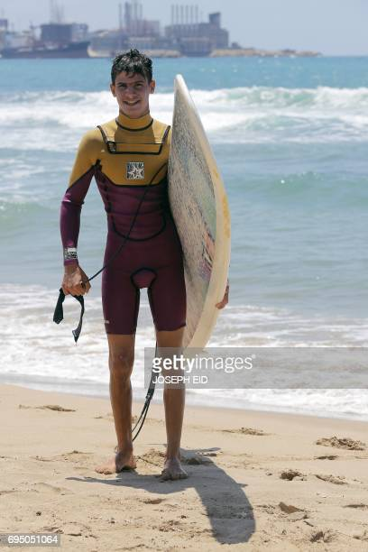 Ali Kassem a 17yearold Syrian refugee smiles for a picture as he carries his surfboard on a beach in the town of Jiyeh south of the Lebanese capital...
