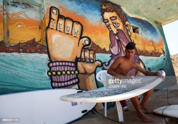 Ali Kassem a 17yearold Syrian refugee waxes his surfboard before going surfing on a beach in the town of Jiyeh south of the Lebanese capital Beirut...