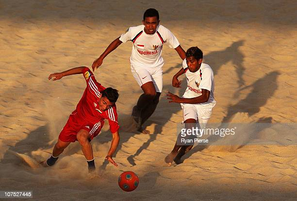 Ali Sleman of Syria competes for the ball against Komang Kariana and Wayan Metra Jaya of Indonesia during the Beach Soccer match between Syria and...