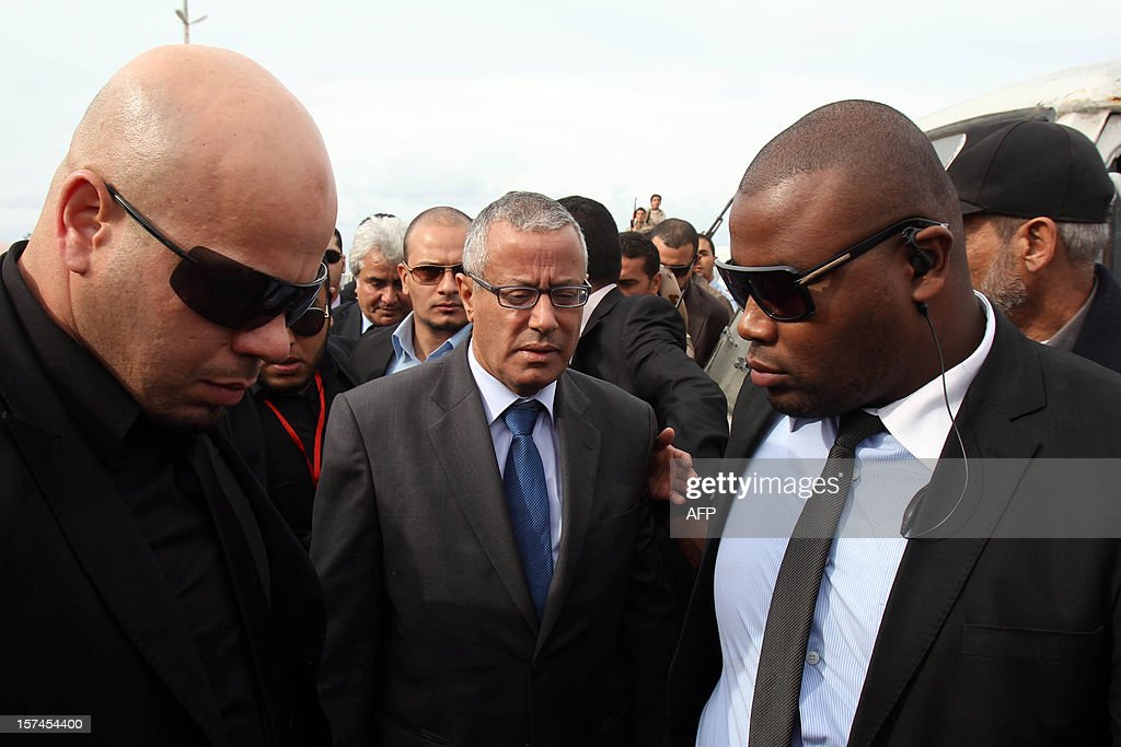 Ali Zaidan (C), prime minister of Libya's interim government, is surrounded by bodyguards as he attends the funeral procession of leading Libyan dissident Mansour al-Kikhia in the eastern Libyan port city of Benghazi on December 3, 2012. Kikhia, who disappeared 19 years ago under the Kadhafi regime, was buried weeks after his body was found in an intelligence services morgue, his brother said.